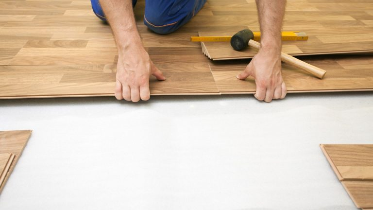 Close up photo of a flooring contractor installing timber flooring in Townsville